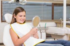 Menina que guarda o espelho na cadeira dos dentistas Fotografia de Stock Royalty Free