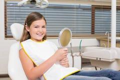 Menina que guarda o espelho na cadeira dos dentistas Fotos de Stock