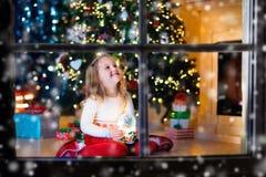 Menina que guarda o globo da neve sob a árvore de Natal Fotografia de Stock Royalty Free