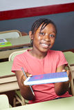 Menina que guarda o livro de escola na classe Fotos de Stock