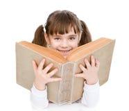 Menina que guarda o livro grande Isolado no fundo branco Fotos de Stock Royalty Free
