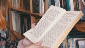 Menina que guarda o livro nas mãos e que lê na biblioteca no fundo das estantes video estoque