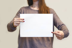 Menina que guarda o papel A4 vazio branco horizontalmente Presenta do folheto Foto de Stock
