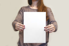 Menina que guarda o papel A4 vazio branco verticalmente Presentati do folheto Fotografia de Stock Royalty Free