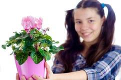 Menina que guarda o potenciômetro de flores cor-de-rosa Imagens de Stock Royalty Free