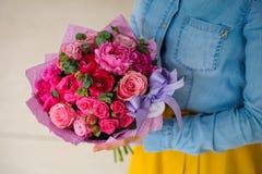 Menina que guarda o ramalhete de umas flores cor-de-rosa e roxas misturadas fotografia de stock royalty free
