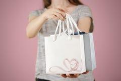 A menina que guarda o saco de papel do presente da placa dois disponivéis com corações zomba u Fotos de Stock Royalty Free