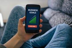 Menina que guarda o telefone esperto com conceito dos objetivos de negócios na tela Foto de Stock Royalty Free
