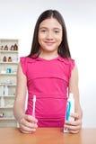 Menina que guarda a pasta da escova de dentes e de dente Imagens de Stock Royalty Free
