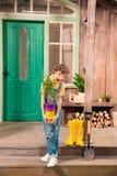 Menina que guarda potenciômetros de flor coloridos com planta home e que olha para baixo Foto de Stock