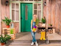 Menina que guarda potenciômetros de flor coloridos com planta home e que sorri na câmera Imagens de Stock