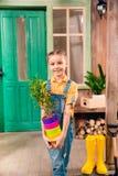 Menina que guarda potenciômetros de flor coloridos com planta home e que sorri na câmera Fotos de Stock Royalty Free
