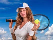 Menina que guarda a raquete e a bola de tênis no céu azul Fotografia de Stock Royalty Free