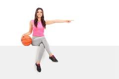 Menina que guarda um basquetebol e que aponta com dedo Fotos de Stock Royalty Free