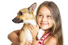 menina que guarda um cão nas mãos foto de stock