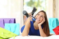Menina que guarda um cartão de crédito que pensa que comprar em casa fotografia de stock royalty free