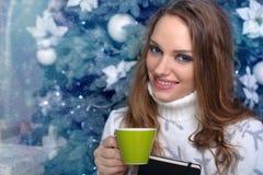 Menina que guarda um livro e que bebe uma bebida morna Imagem de Stock Royalty Free