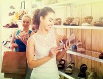 Menina que guarda um par de sapatas escolhido no boutique Foto de Stock