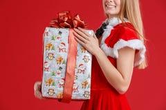 Menina que guarda um presente com uma curva vermelha que está o close-up lateral em um fundo vermelho fotos de stock