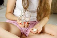 Menina que guarda um vidro da água e dos comprimidos closeup Fotografia de Stock