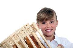 Menina que guarda uma cesta do pão Imagens de Stock