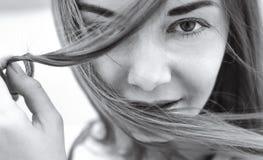 Menina que guarda uma costa do cabelo e dos olhares na câmera Fim-u Foto de Stock