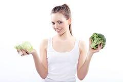 Menina que guarda uma couve verde e uns brócolis foto de stock