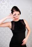 A menina que guarda uma mão com dedos espalhou em torno dos olhos Fotos de Stock