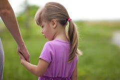 Menina que guarda uma mão de sua mãe Conce das relações de família imagens de stock