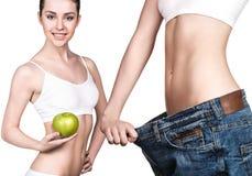 Menina que guarda uma maçã e que veste calças de brim grandes imagem de stock royalty free