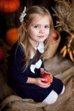 Menina que guarda uma maçã em um interior do outono fotografia de stock royalty free