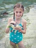 Menina que guarda uma tartaruga de mar do bebê Fotos de Stock