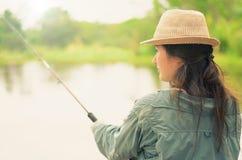 Menina que guarda uma vara de pesca, pescando em um lago Foto de Stock Royalty Free