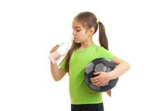 A menina que guardam uma bola em sua mão e as bebidas molham de uma garrafa Foto de Stock Royalty Free