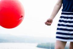 Menina que guardara o balão vermelho Imagem de Stock