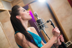 Menina que guardara um microfone e que canta Imagens de Stock