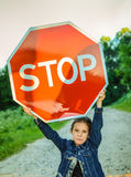 Menina que guardara um sinal vermelho Fotos de Stock Royalty Free