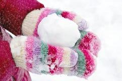 Menina que guardara um snowball Imagens de Stock Royalty Free