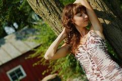 Menina que inclina-se de encontro à árvore fotos de stock royalty free