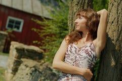 Menina que inclina-se de encontro à árvore fotografia de stock