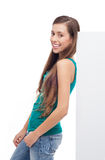 Menina que inclina-se de encontro ao poster em branco Fotografia de Stock
