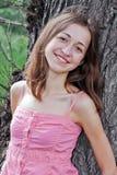 Menina que inclina-se em uma árvore Fotografia de Stock