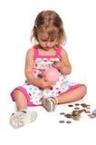 Menina que introduz moedas no banco Piggy Imagem de Stock Royalty Free