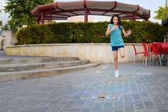 Menina que joga amarelinha o jogo no asfalto no campo de jogos fotografia de stock