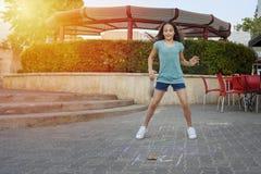 Menina que joga amarelinha o jogo no asfalto no campo de jogos imagens de stock
