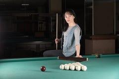 Menina que joga bilhar mulher que guarda a vara de sugestão fotografia de stock royalty free