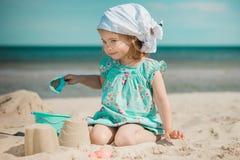 Menina que joga com a areia na praia Fotos de Stock Royalty Free