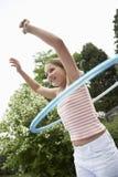 Menina que joga com a aro de Hula no quintal fotos de stock royalty free