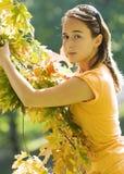 Menina que joga com as folhas Fotos de Stock Royalty Free