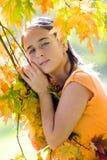 Menina que joga com as folhas Fotos de Stock